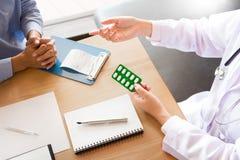 Aggiusti la compressa della tenuta della mano della droga e spieghi al paziente dentro uff fotografie stock libere da diritti
