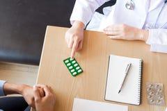 Aggiusti la compressa della tenuta della mano della droga e spieghi al paziente dentro uff fotografie stock