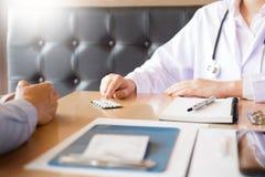 Aggiusti la compressa della tenuta della mano della droga e spieghi al paziente dentro uff immagine stock