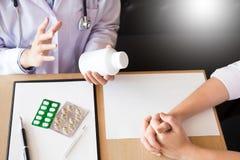Aggiusti la compressa della tenuta della mano della droga e spieghi al paziente dentro uff immagine stock libera da diritti