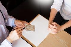 Aggiusti la compressa della tenuta della mano della droga e spieghi al paziente dentro uff immagini stock