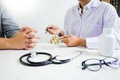 Aggiusti la compressa della tenuta della mano della droga e spieghi al paziente in hos immagine stock