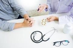 Aggiusti la compressa della tenuta della mano della droga e spieghi al paziente in hos immagine stock libera da diritti