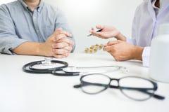 Aggiusti la compressa della tenuta della mano della droga e spieghi al paziente in hos fotografie stock libere da diritti