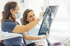 Aggiusti la conversazione con il suo paziente e l'insegnamento della radiografia Fotografie Stock