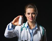 Aggiusti la donna che mostra la bottiglia della medicina su fondo nero Immagini Stock