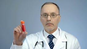 Aggiusti la fiala della tenuta con il campione di sangue donato per l'analisi, consapevolezza di HIV Fotografia Stock