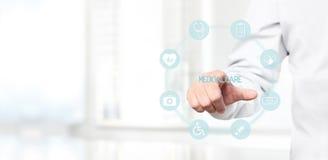 Aggiusti la mano che tocca le icone mediche sullo schermo virtuale Immagine Stock Libera da Diritti