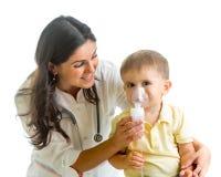 Aggiusti la maschera dell'inalatore della tenuta per il bambino che respira, ospedale Immagini Stock