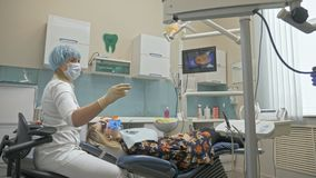 Aggiusti la micro macchina fotografica intraorale speciale usata di Digital ai denti dell'esame Sul monitor il dentista ed il paz stock footage