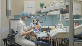Aggiusti la micro macchina fotografica intraorale speciale usata di Digital ai denti dell'esame Sul monitor il dentista ed il paz video d archivio