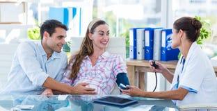 Aggiusti la presa della pressione sanguigna di un paziente incinto con il suo marito Fotografie Stock