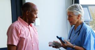 Aggiusti la spiegazione circa il monitor di pressione sanguigna all'uomo senior 4k video d archivio