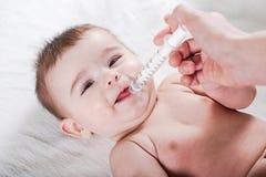 Aggiusti le elasticità una certa medicina ad un piccolo bambino immagini stock libere da diritti