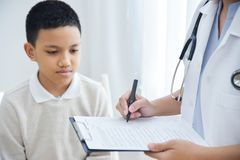 Aggiusti prendere nota sulla lista di controllo per i pazienti di un ragazzino fotografia stock