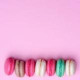Agglutini il macaron o il maccherone sul fondo del turchese da sopra, biscotti di mandorla variopinti, i colori pastelli, la cart Fotografie Stock