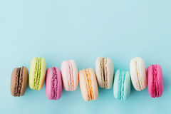 Agglutini il macaron o il maccherone sul fondo del turchese da sopra, biscotti di mandorla variopinti, vista superiore Fotografia Stock