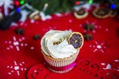 Agglutini, stando su un tovagliolo rosso di Natale su una tavola di legno bianca circondata da una ghirlanda verde e dalle luci d Fotografia Stock Libera da Diritti