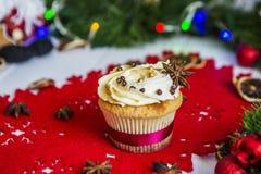 Agglutini, stando su un tovagliolo rosso di Natale su una tavola di legno bianca circondata da una ghirlanda verde e dalle luci d Fotografie Stock