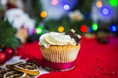 Agglutini, stando su un tovagliolo rosso di Natale su una tavola di legno bianca circondata da una ghirlanda verde e dalle luci d Immagine Stock Libera da Diritti