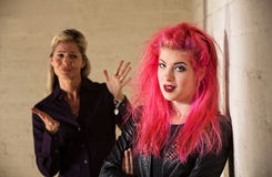 Aggravated Parent with Child. Angry mother with frustrated daughter in pink hair Royalty Free Stock Photos