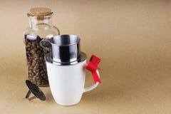 Aggredisca con il dispositivo di gocciolamento del caffè e un barattolo di vetro dei chicchi di caffè Immagine Stock Libera da Diritti