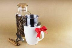 Aggredisca con il dispositivo di gocciolamento del caffè e un barattolo di vetro dei chicchi di caffè Fotografia Stock
