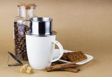 Aggredisca con il dispositivo di gocciolamento del caffè, i biscotti e un barattolo di vetro dei chicchi di caffè Fotografia Stock