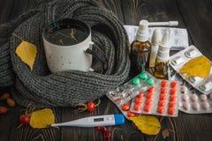 Aggredisca con tisana e freddo, medicina di influenza su una tavola di legno Il termometro con temperatura elevata Fogli di cadut Fotografia Stock