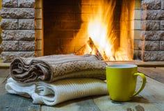 Aggredisca per tè o caffè, cose di lana vicino al camino accogliente Fotografia Stock Libera da Diritti