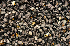 Aggregate of coarse dark grey stones creating a gravel / grit pattern. A closeup of a pile of loose rough stones taken at a stone pit. The gravel / grit has been Royalty Free Stock Photos