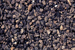 Aggregate of dark coarse gray stones crushed at a stone pit - gravel pattern. A close-up of a pile of loose rough stones taken at a stone pit. The gravel / grit Stock Photography