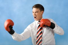 Aggression. Portrait of screaming boxer wearing red gloves over blue background Stock Photo