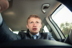 Aggression behind the wheel, the driver is surprised while drivi Stock Photography