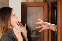 Aggression when a burglar try to attack a housewife. With a hand through the door at home royalty free stock photography