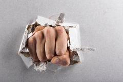 Aggression concept, wall is broken through by a fist Royalty Free Stock Image