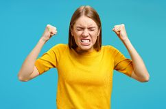 Aggression girl with widely open mouth and clenched teeth holds hands clenched in fists. Photo of girl in yellow sweater on blue background. Emotions and royalty free stock image