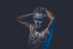 Aggression, naked man covered with paint and mud skin Royalty Free Stock Image