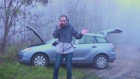 Aggressiv chaufför av en gammal bil som skriker in i mobiltelefonen Det är dags att ändra bilen till ny lager videofilmer