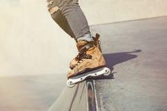 Aggressiv inline rollerblader som maler på ramp i skatepark Fotografering för Bildbyråer