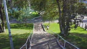 Aggressiv inline rullbladerplugghäst på stången i skatepark utanför gem Öva för sport för sommar som extremt är utomhus- in royaltyfri bild
