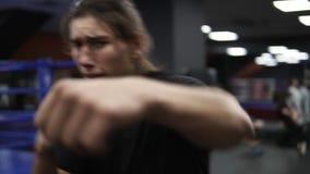 Aggressiv lång haired manutbildning nära boxningsringen i modern idrottshall Slåss skuggan Kickboxer i svart T-tröja och lager videofilmer