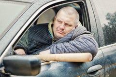 Aggressiv man med ett baseballslagträ i bil på utomhus Royaltyfri Fotografi