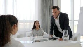 Aggressiv mentor med kollaboratörer i affärsmitt, kontorsfolk på jobbet, stående av den rageful ledaren på tabellen, lager videofilmer