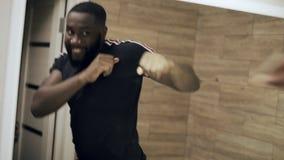 Aggressiv svart man som framme boxas av spegeln på badrummet lager videofilmer