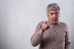 An aggressive adult man with gray hair and wide open eyes pointing at you with finger. Emotional senior man wearing sweater standi. Ng over white background Stock Photos