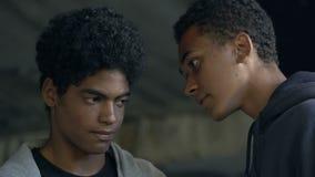 Aggressive Afro-American male teenager threatening boy in dark lane, bullying