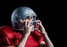 Aggressive american football player holding his helmet. Against black background Royalty Free Stock Photography