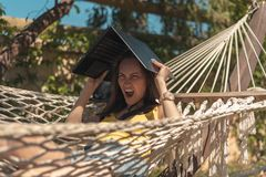 Aggressive, angry, dissatisfied woman in a yellow swimsuit lying in a hammock holding a laptop over her head, no connection, no In. Ternet, no Wi Fi, summer heat stock photo
