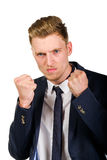 Aggressive angry young businessman raised hands and squeezed fists. On white Royalty Free Stock Photo